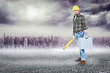 Composite image of manual worker with spirit level and toolbox