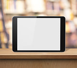 tablet PC on wood shelf in book shop or library