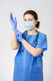 Doctor putting on blue surgical gloves