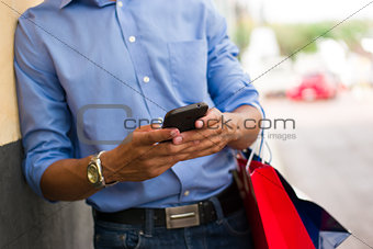 African American Man Typing Message On Phone Shopping Bags