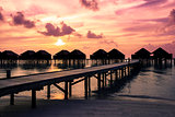Maldives sunset with water villas silhouette