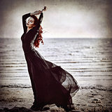 Beautiful goth girl standing on sea coast. Grunge texture effect
