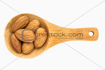 almond nuts on wooden spoon