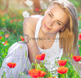 Beautiful girl on poppy flower field
