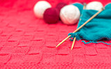 yarn balls and spokes on knitted fabric close-up