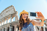 Woman tourist taking selfie at Colosseum in Rome in summer
