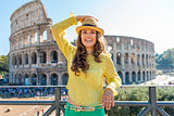 Smiling woman holding hat near Colosseum in Rome in summer