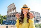 Woman standing near Colosseum in Rome removing earbuds