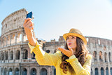 Woman tourist taking selfie blowing kisses at Rome Colosseum