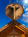 Cross on Tree Trunk with Wooden Church