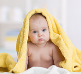 baby girl under towel after bath