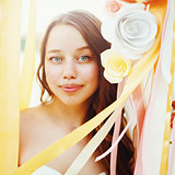 Beautiful bride among paper flowers decoration