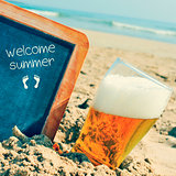 beer and chalkboard with the text welcome summer, on the sand of