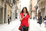 Fashion woman walking and using a smart phone