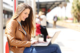 Girl using a laptop while waiting in a train station