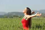 Woman breathing deep fresh air in a field
