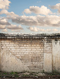 Blue sky with clouds behind the cracked wall