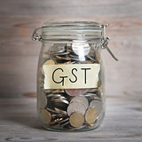 Coins in money jar with gst labe