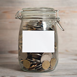 Coins in glass money jar with white blank label