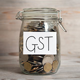 Coins in glass money jar with gst label
