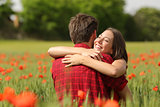 Couple hugging after proposal in a flower field