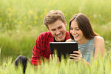 Couple watching videos in a tablet in a field
