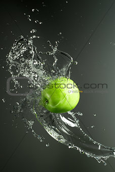 Green apple with water splash, on black