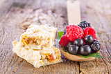 muesli bars with fresh berries in spoon on wooden