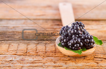 blackberries with spoon on wooden background