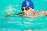 swimmer in blue cap and goggles swimming in the pool