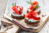 Snack rye bread, soft cheese with herbs and salted red salmon.