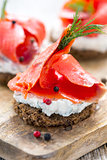Sandwich of black bread, cheese with herbs and red salmon.