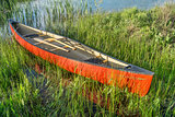 red canoe with wooden paddles