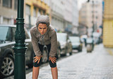 Woman runner in the rain taking a break and stretching