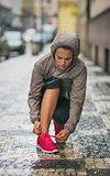 Woman runner kneeling down to tie running shoe in rain
