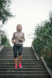 Woman jogger running down steps listening to music