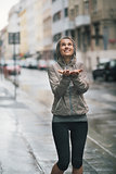 Athletic, happy woman holding her hands out to catch rain drops