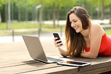 Girl using a laptop and smart phone in a park
