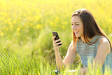 Woman using a smart phone in a green field