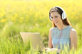 Woman with a laptop and headphones in a field