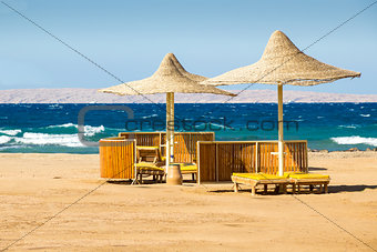 Wattled sun umbrellas and benches on the deserted beachю
