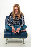 Beautiful stylish young woman sitting cross-legged on a couch