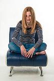 Beautiful stylish young woman sitting cross-legged on a couch