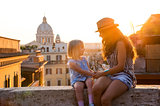 Mother and daughter sitting on ledge at sunset in Rome