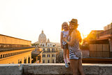 Mother holding daughter standing on ledge at sunset in Rome