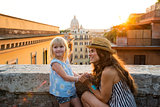 Mother kneeling by daughter above Rome at sunset
