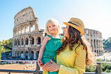 Smiling mother and daughter with Colosseum in background