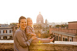Smiling mother and daughter at sunset in Rome, St. Peter's