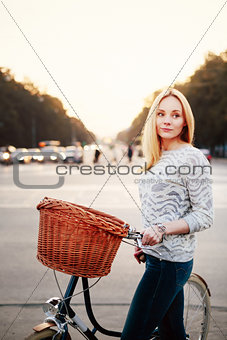Calm woman on a vintage bicycle in the city