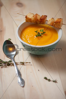 Bowl of pumpkin soup on  wood table